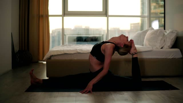 Yogi blonde girl doing monkey asana or stretching lags performing split then back lotus pose with hands in namaste. Woman exercising in her home living room Yogi blonde girl doing monkey asana or stretching lags performing split then back lotus pose with hands in namaste. Woman exercising in her home living room. doing the splits stock videos & royalty-free footage
