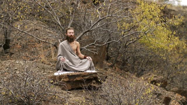 Yogi meditating at mountains in autumn