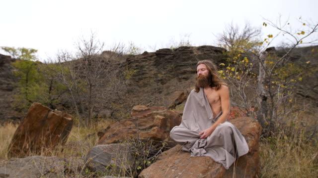 Yogi sitting on the rock in meditation