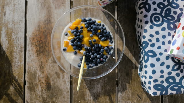 vídeos de stock e filmes b-roll de yogurt bowl with blueberries and mango, gift boxes on the side - engradado