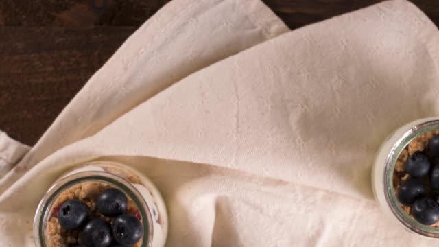 ブルーベリーとミューズのヨーグルトパフェ。木製のテーブルの上に装飾スプーンとメイソンジャーで提供健康的な朝食のコンセプト。 - パフェ点の映像素材/bロール