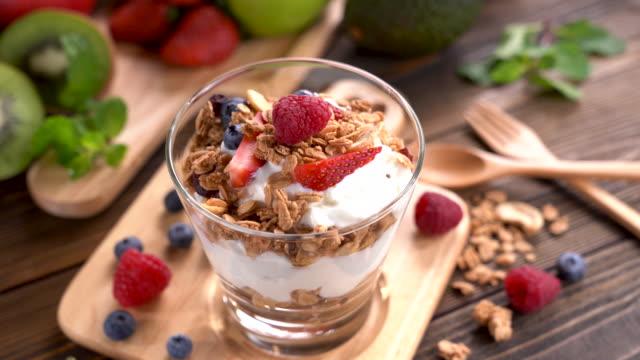 yogurt with granola and fruits in glass on wooden table - łyżka sztućce filmów i materiałów b-roll