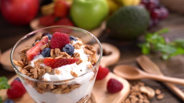 yogurt with granola and fruits in glass on wooden table - gotowy do jedzenia filmów i materiałów b-roll