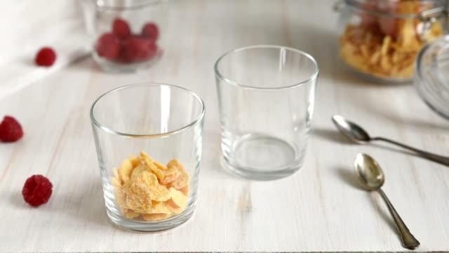 ラズベリーとグラノーラのヨーグルトをグラス瓶に入れた - パフェ点の映像素材/bロール