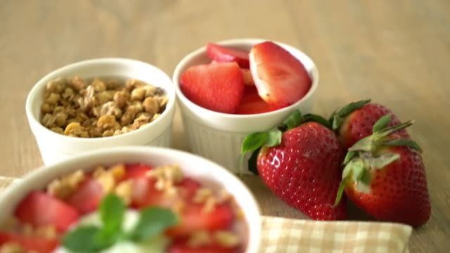 vídeos de stock e filmes b-roll de yogurt with strawberry and granola - oats