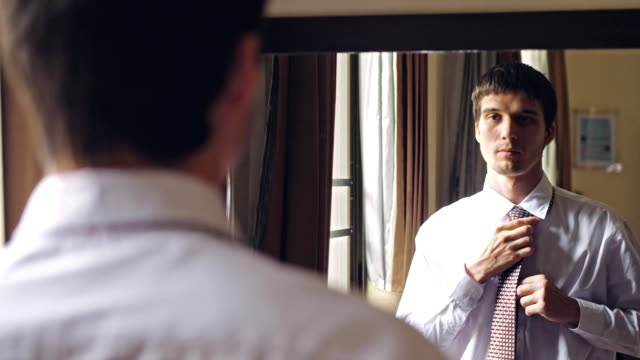 yomg handsome man in white shirt stands by the mirror tying a tie. to chenges focus from man to the mirror. 3840x2160 - затягивание стоковые видео и кадры b-roll