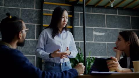 yong donna asiatica che parla e discute nuove idee con il team creativo durante il brainstorming di progetti di start-up in ufficio moderno al chiuso - abbigliamento casual video stock e b–roll