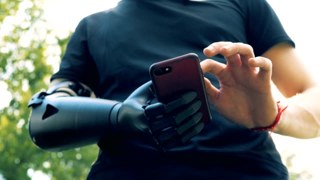 Yong man with an artificial hand using smartphone. Future concept. Yong man with an artificial hand using smartphone. 4K. prosthetic equipment stock videos & royalty-free footage