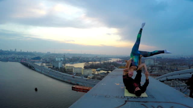 Yong woman and man doing extreme stunts on top of bridge, fantastic city view video