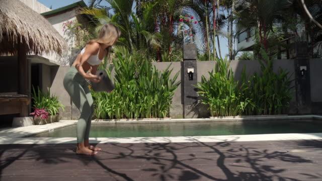 Yong Woman Doing Yoga in Tropical Backyard Garden