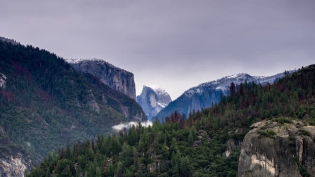Yosemite National Park in Winter - Time Lapse Time lapse of a wintry scene in Yosemite National Park, California. Half dome, covered in snow, is in the centre. national landmark stock videos & royalty-free footage