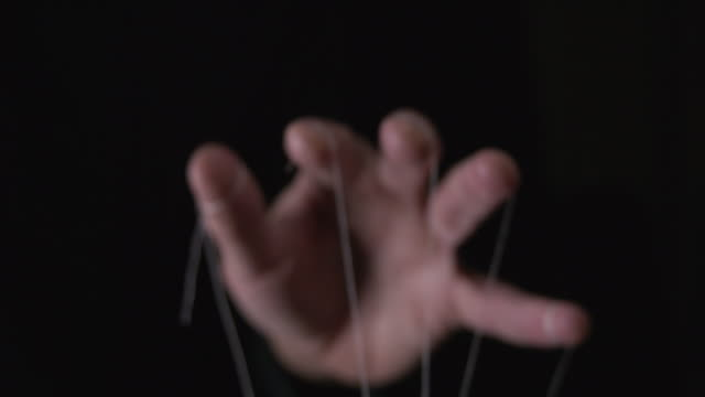 You are being manipulated concept with puppeteer hand and string We are being manipulated concept. Large scary hands with puppet string tied around fingers marionette stock videos & royalty-free footage