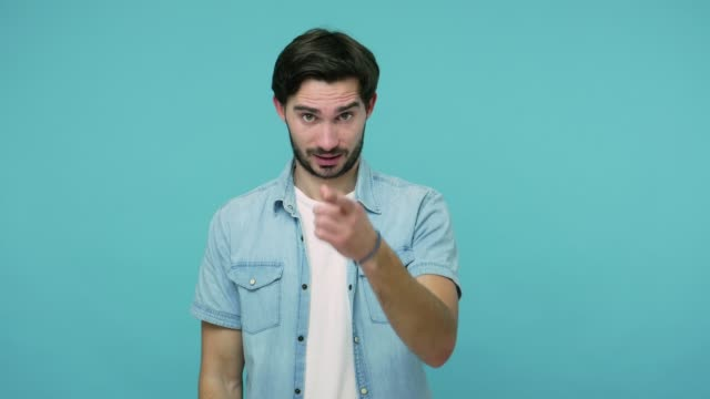 vídeos de stock e filmes b-roll de you are out of mind! bearded guy in jeans shirt showing stupid gesture and pointing to camera, blaming for insane plan - ignorância