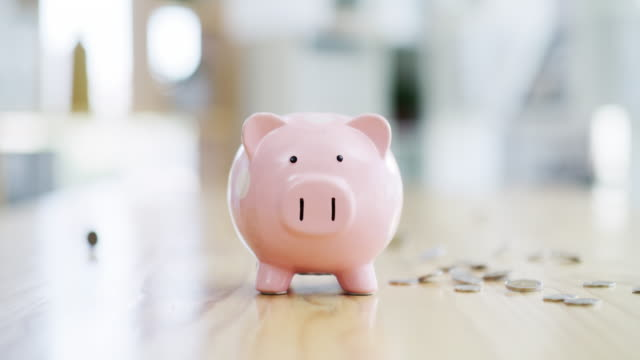 You never know when you might need it 4k video footage of a piggybank on a table with coins falling around it financial planning stock videos & royalty-free footage