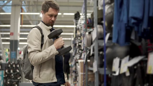 yougn sportsman buys new dumbbell. - sprzęt sportowy filmów i materiałów b-roll