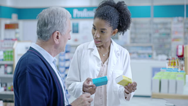 You'll need to take these one three times a day 4k video footage of a young pharmacist helping a senior man in a pharmacy pharmacist stock videos & royalty-free footage