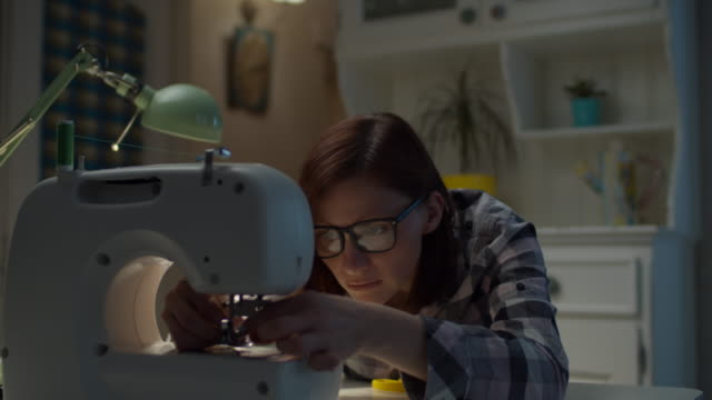 young 30s woman adjusting sewing machine working at home. female seamstress in glasses sewing sitting in living room at home. - sarta video stock e b–roll