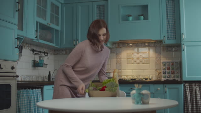 young 30s woman holding paper bag with fresh food on kitchen. happy female unpacking vegetables and baguette from plastic free bag to dinning table. - grocery home video stock e b–roll