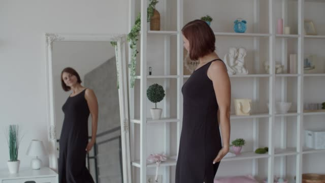 young 30s women putting on long black dress in mirror and admiring with reflection. happy female adult in black dress in bedroom in slow motion - szczupły filmów i materiałów b-roll