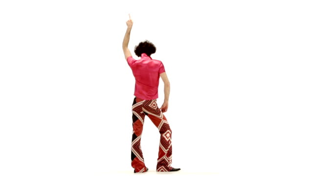 Young 70s curly hair man dressing fuchsia vintage shirt and bell bottoms make dance steps on 103 bpm music track - isolated-on-white HD video footage video