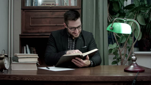 Young academic reading a book and sarcastically nodding his head video
