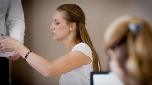 vidéos et rushes de un jeune comptable passe les documents pour un avocat, une femme ressemble étroitement à feuilles de papier avec des informations juridiques importantes - notaire