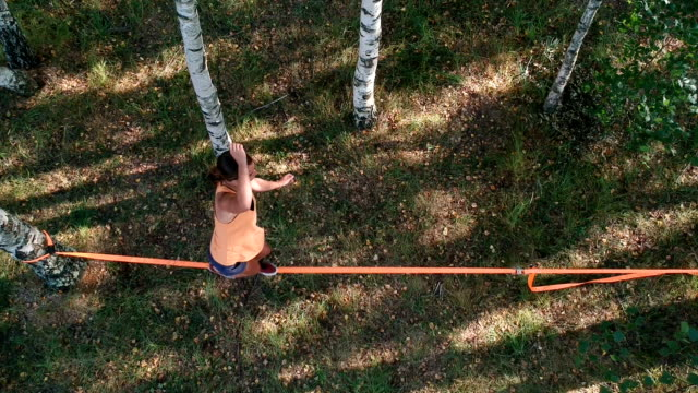 young acrobatic woman have a training in the nature.drone footage