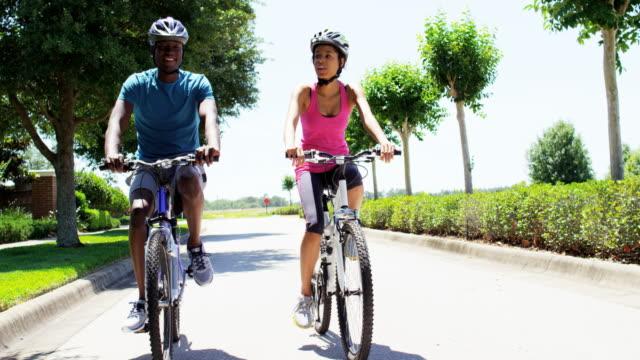 vídeos de stock e filmes b-roll de young active african american couple enjoying biking outdoor - helmet motorbike