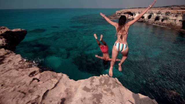 Young active couple jumping off cliff and diving into ocean Young couple on tropical island summer vacations jumping off cliff and diving into sea cliff jumping stock videos & royalty-free footage