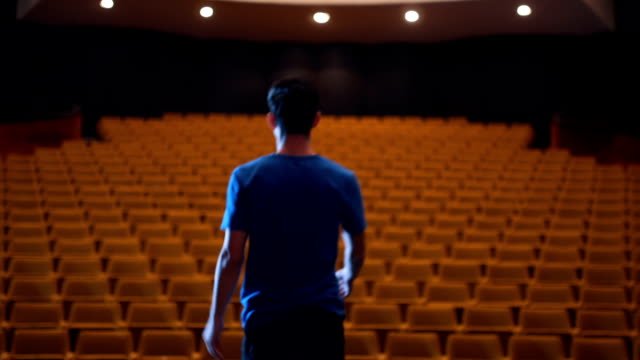 Young actor bowing to the empty theater There is one young man, age 23. He is in theater and he have a rehearsal. He is an actor,he read and learn his text. stage theater stock videos & royalty-free footage