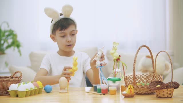 Young adorable boy is sitting at the table full of Easter decorations and is playing with Easter bunnies in his hands. Bunnies' discussion. Who would paint an egg Bunny chooses green colour. Bunny theatre.
