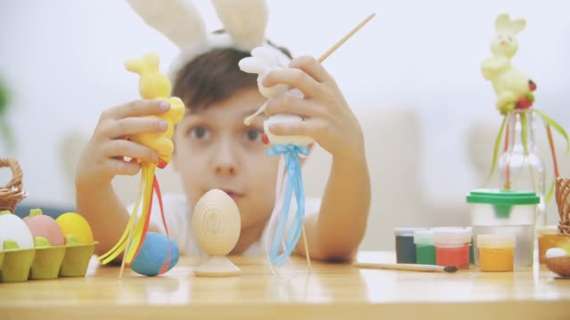 Young adorable boy is sitting at the table full of Easter decorations and is playing with Easter bunnies in his hands. Bunnies' discussion. Who would paint an egg Bunny theatre.