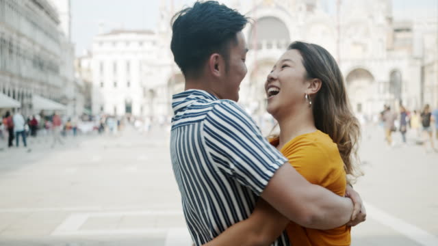 Young adult asian couple kissing and hugging in Venice, Italy
