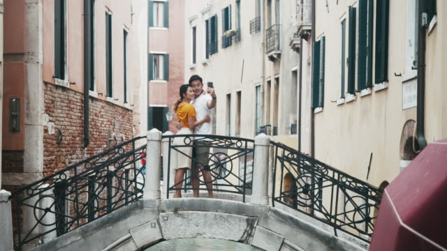 Young adult asian couple taking a selfie in Venice, Italy