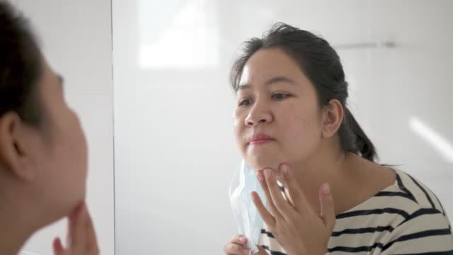 stockvideo's en b-roll-footage met de jonge volwassen aziatische vrouw maakt zich ongelukkig met huidacne of puistjes van het dragen van gezichtsmasker dat gezwollen, vlek, litteken, huidallergie op kin en wang in spiegel in maskne covid-19 sociale afstandsconcept toont. - mirror mask