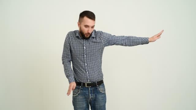 stockvideo's en b-roll-footage met jong volwassen baard man plezier dansen op een grijze achtergrond - studio