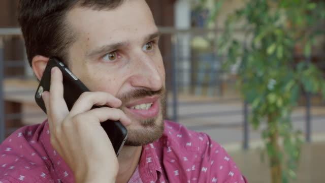 unga vuxna skäggig man pratar på smartphone i café - telefonmeddelande bildbanksvideor och videomaterial från bakom kulisserna
