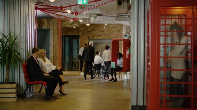 アシスタントとモダンオフィスコリドーに乗って車椅子の若い大人のビジネスマン - ワイドドリーショット(トラックアウト) - disabilitycollection点の映像素材/bロール