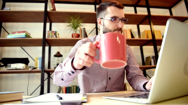 Young adult businessman working on laptop and drinking something a man with a beard in a fashionable shirt sitting at the table. It prints on a laptop. then interrupted, drinking tea or coffee, and continues to print. the atmosphere of work and employment. close-up. one person. the camera moves from left to right. slider. in the background with books shelves coworking stock videos & royalty-free footage