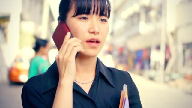 junge erwachsene geschäftsfrau nutzt smartphone am tag auf stadtstraße - himachal pradesh stock-videos und b-roll-filmmaterial