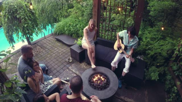 Jovens adultos fogueira violão cantando festa na piscina ao ar livre Summer BBQ - vídeo