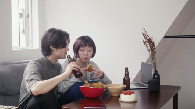 Young adult couple eating fried chicken and drinking beer on Christmas
