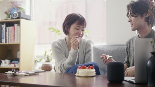 Young adult couple eating japanese strawberry sponge cake on Christmas