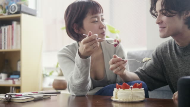 giovane coppia adulta che mangia pan di spagna alla fragola giapponese a natale - coppia eterosessuale video stock e b–roll