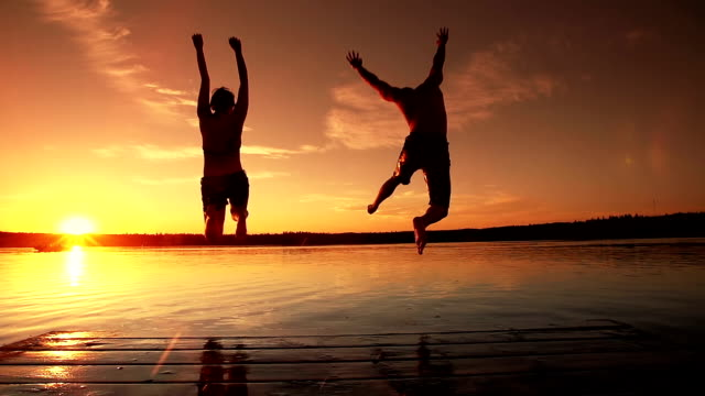 Young adult couple jumps into lake. Video of a young adult couple running and jumping into a lake at sunset.   The immense sense of freedom and joy are very apparent in this fun clip.   The relationship that these 2 people enjoy together will last a lifetime.   Life is enjoyed while taking part in recreation.  Well being is a part of a healthy lifestyle, and these two are experiencing life to the full.   It's a beautiful warm summer evening and life is good. love emotion stock videos & royalty-free footage