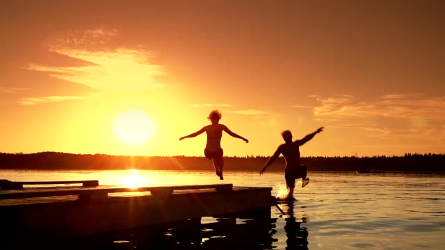 Young adult couple jumps into lake. Video of a young adult couple running and jumping into a lake at sunset.   The immense sense of freedom and joy are very apparent in this fun clip.   The relationship that these 2 people enjoy together will last a lifetime.   Life is enjoyed while taking part in recreation.  Well being is a part of a healthy lifestyle, and these two are experiencing life to the full.   It's a beautiful warm summer evening and life is good. satisfaction stock videos & royalty-free footage