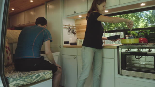 UHD 4K: Young adult couple living alternatively in a van home Young adult couple living alternatively in a van home rv interior stock videos & royalty-free footage