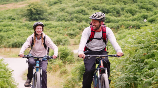 Young adult couple riding mountain bikes in the countryside during a camping holiday, Lake District, UK