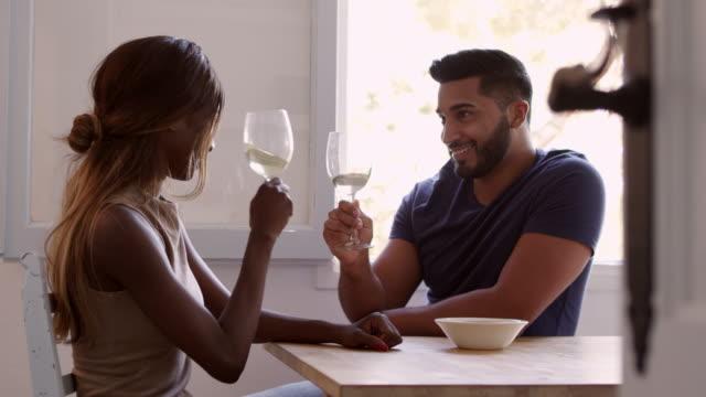 若い大人カップル飲みワインに座るし、r3d のショットの台所で話して - 対面点の映像素材/bロール
