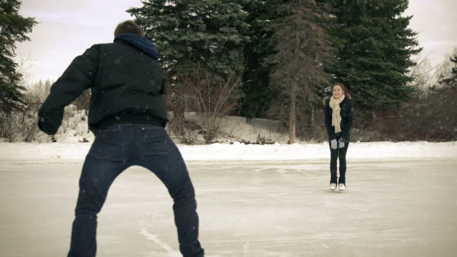 Young adult couple skating together in winter.. video